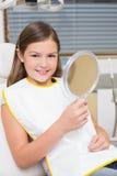 Espejo de la tenencia de la niña en silla de los dentistas Imagenes de archivo