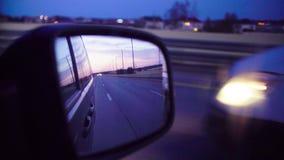 Espejo de la vista posterior en un coche móvil en la tarde metrajes