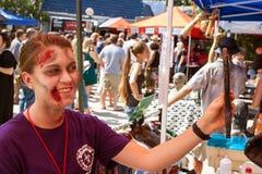 Espejo de las aplicaciones de la mujer para comprobar hacia fuera maquillaje del zombi en el evento Fotos de archivo