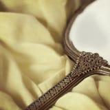 Espejo de mano antiguo sobre tela suave Fotos de archivo