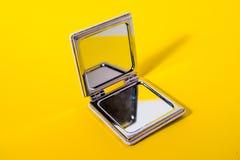 Espejo de mano en fondo amarillo imagen de archivo libre de regalías