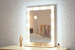 Espejo del maquillaje en la tabla cerca de la pared blanca en sitio foto de archivo libre de regalías