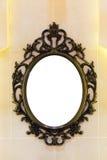 Espejo del vintage con el marco clásico del metal en la pared Foto de archivo libre de regalías