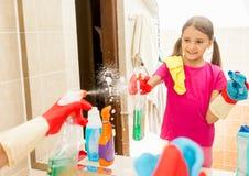 Espejo sonriente de la limpieza de la muchacha en el cuarto de baño con el espray y el paño Fotos de archivo libres de regalías