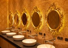 Espejos de oro sobre los lavabos en el cuarto de baño imagenes de archivo