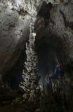 Espeleólogo en cueva que admira la estalagmita grande Fotografía de archivo libre de regalías
