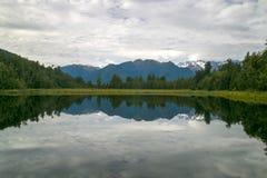 Espelho calmo natural da água do céu nebuloso, das montanhas, dos montes e da floresta, lago Matheson na costa oeste, geleira do  imagem de stock