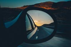 Espelho de carro com céu azul e o sol vermelho acima da estrada Fotos de Stock Royalty Free