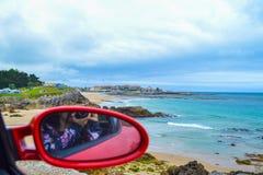 Espelho de rearview Defocused de um carro vermelho com Comillas Cantábria, imagem de stock royalty free