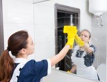 Espelho do banheiro que está sendo limpado para baixo pela empregada doméstica Fotografia de Stock