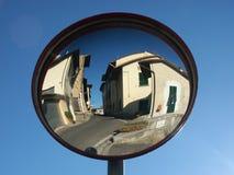 Espelho do tráfego que reflete a cidade pequena Fotografia de Stock