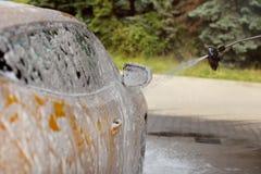 Espelho lateral e lateral do carro amarelo que está sendo lavado no serviço do auto Fotos de Stock