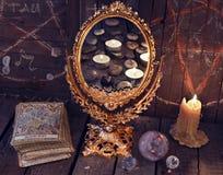 Espelho mágico com cartões de tarô e velas ardentes Foto de Stock