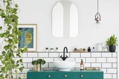 Espelho na parede branca acima da bacia verde no interior do banheiro com plantas e cartaz Foto real imagens de stock royalty free