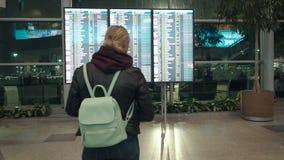 A espera da menina para a partida no aeroporto, a partida e as chegadas embarcam, exposição eletrônica do calendário do aeroporto filme