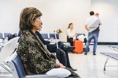 Espera da mulher assentada na sala de estar da partida do ` s do aeroporto foto de stock royalty free