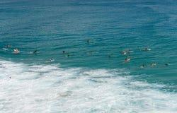 Espera de las personas que practica surf para la onda perfecta Imagen de archivo libre de regalías