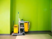 Espera do carro das ferramentas da limpeza para limpar Cubeta e grupo de equipamento da limpeza no escritório foto de stock