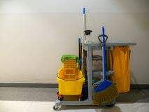 Espera do carro das ferramentas da limpeza para o líquido de limpeza Cubeta e grupo de equipamento da limpeza no armazém serviço  fotografia de stock