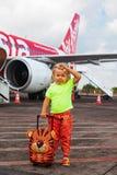 Espera linda del niño para subir al avión en el aeropuerto internacional de Bali imagen de archivo