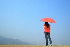 Espera roja de la mujer del paraguas para el cielo alguien y de la nube Fotos de archivo