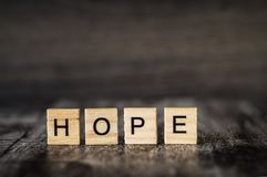 A esperança da palavra é feita de cubos de madeira brilhantes com letras pretas sobre Foto de Stock Royalty Free