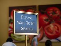 Espere por favor para ser muestra asentada que se coloca en el frente de un restaurante imagen de archivo
