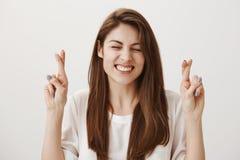 Espere que apruebe el examen Retrato de hacer muecas a la muchacha europea emocionada que aumenta las manos con los fingeres cruz imagenes de archivo