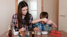 Esperimenti su chimica a casa La madre ed il figlio fanno insieme un esperimento di scienza stock footage
