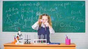 Esperimento astuto della scuola di comportamento dello studente della ragazza Liquidi chimici di studio dell'allievo della scuola fotografie stock