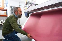 Espertise man i plottare för överföringsprintingbransch arkivbild