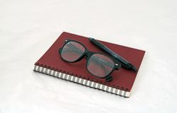 Espetáculos e a pena na obscuridade - o livro de nota vermelho e o anel preto da espinha registram fotos de stock