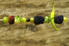 Espetos com fruto natural na madeira borrada do fundo Fotos de Stock
