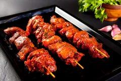 Espetos da carne de porco a grelhar e assar Ainda vida no fundo preto Fotos de Stock Royalty Free