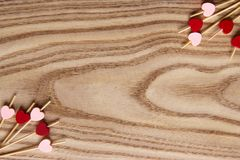Espetos de madeira vermelhos e cor-de-rosa para o alimento com um coração Fundo de madeira para o dia do ` s do Valentim do st Co foto de stock royalty free