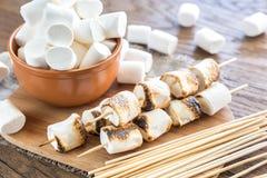 Espetos do marshmallow na placa de madeira fotografia de stock