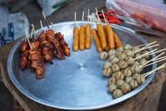 Espetos grelhados da carne de porco e da galinha para a venda em Tailândia imagem de stock