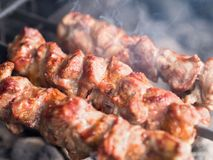 Espetos grelhados da carne nos carvões, com fumo Alimento da rua foto de stock
