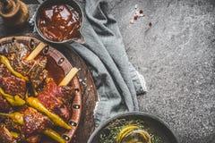 Espetos picantes da carne com molho de assado no fundo rústico da mesa de cozinha, vista superior Foto de Stock Royalty Free
