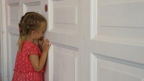 Espião pequeno que espreita através da porta