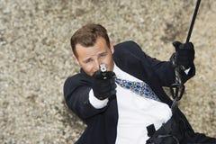 Espião que Rappelling e que aponta a arma Imagens de Stock Royalty Free