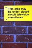 Espiar amarelo brilhante da parede de tijolo vermelho do sinal da fiscalização Imagens de Stock