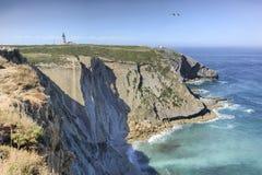 Espichel cape lighhouse, Sesimbra, Portugal. Espichel Cape lighthouse building over rocky cliffs,  Sesimbra, Portugal Stock Image