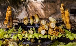 Espigas de milho roasted na grade Alimento da rua foto de stock