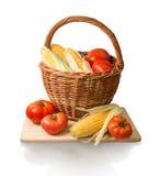 Espigas do milho e dos tomates na cesta Fotografia de Stock