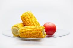 Espigas e tomate de milho em uma placa de vidro. DOF pequeno Imagens de Stock Royalty Free
