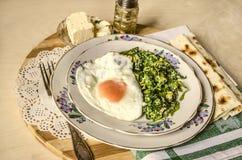 Espinaca con los huevos fritos y el queso de las ovejas, pita en la tajadera rayada Imagenes de archivo