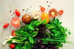 Espinaca fresca, cebolla verde, albahaca, hierbas, eneldo y tomates en el fondo concreto gris, foco selectivo Visión superior ent fotos de archivo libres de regalías