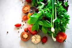 Espinaca fresca, cebolla verde, albahaca, hierbas, eneldo y tomates en el fondo concreto gris, foco selectivo Visión superior ent imagen de archivo