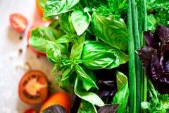 Espinaca fresca, cebolla verde, albahaca, hierbas, eneldo y tomates en el fondo concreto gris, foco selectivo Visión superior ent foto de archivo